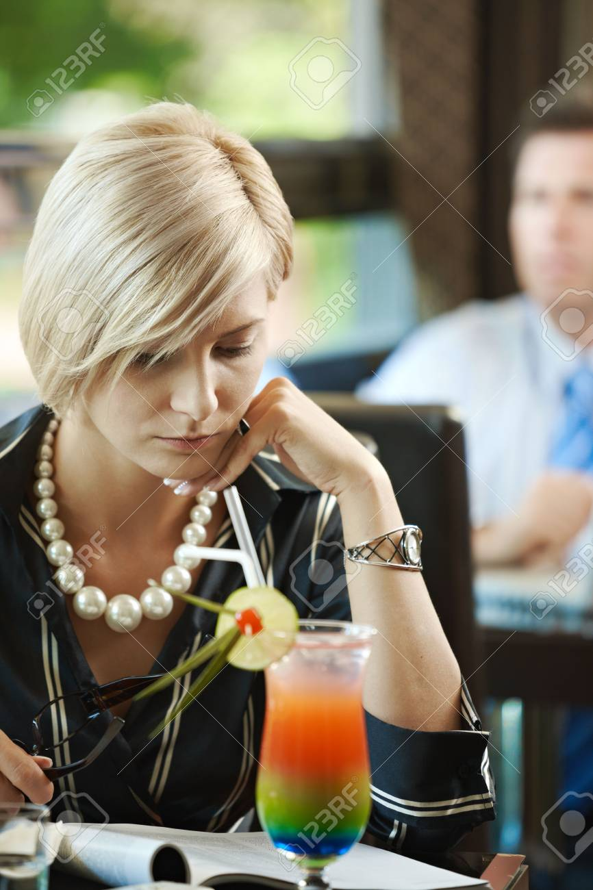 Young woman sitting at table in cafe, reading magazine. Stock Photo - 5783691