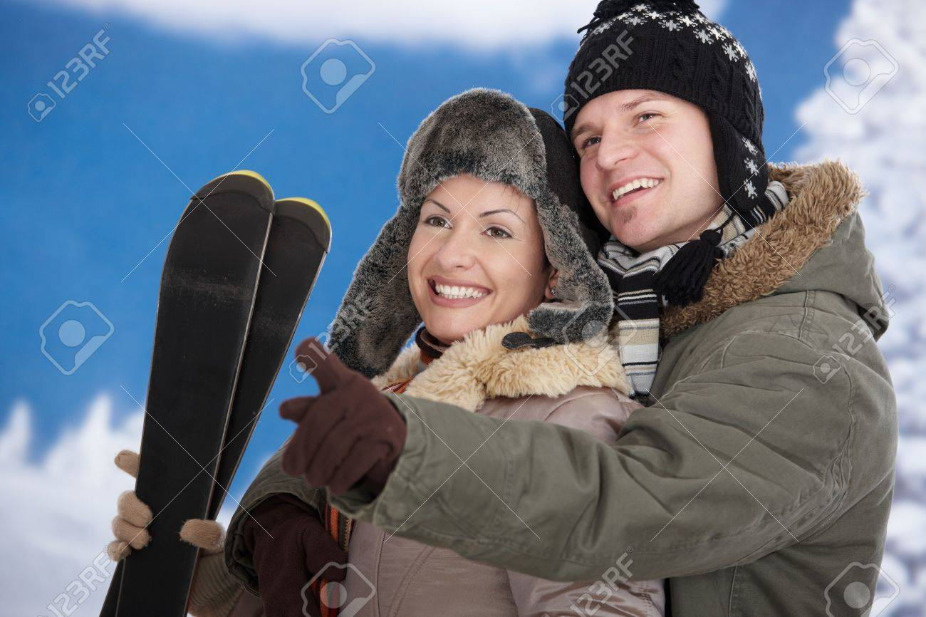 Happy couple in snow at winter wearing warm clothes, smiling. Woman holding skis. Stock Photo - 5806443