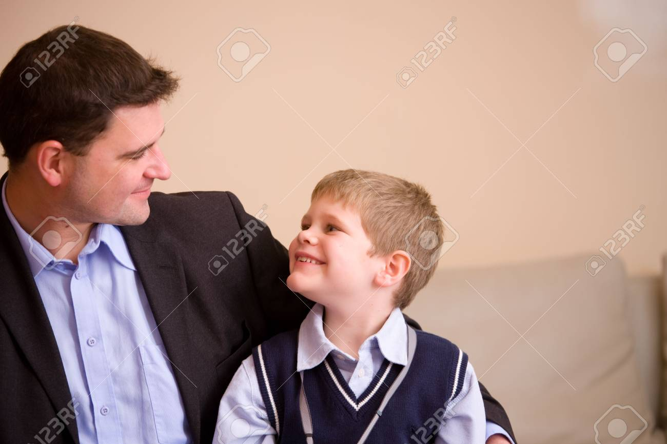 Happy father and son sitting together on couch at home, looking at each other, smiling. Stock Photo - 5827822