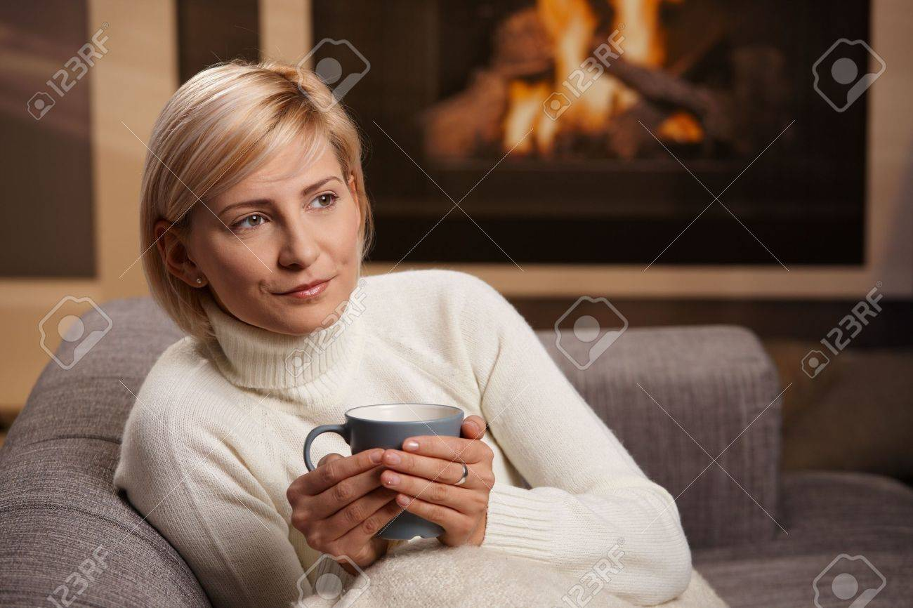 Woman sitting on sofa at home drinking hot tea, looking away. Stock Photo - 5851127