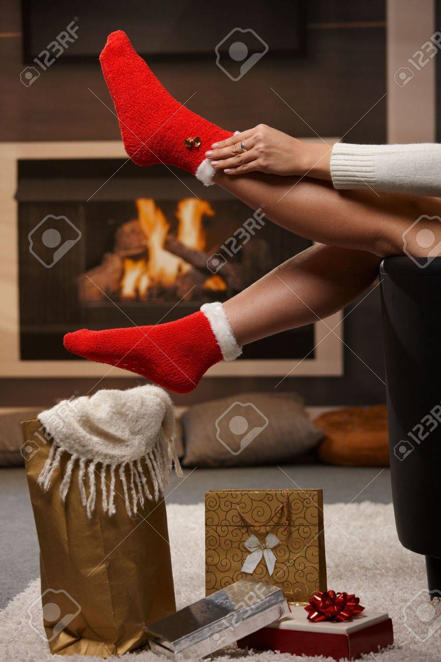 Female legs in santa claus socks at christmas in front of fireplace. Gifts on the floor. Stock Photo - 5865748
