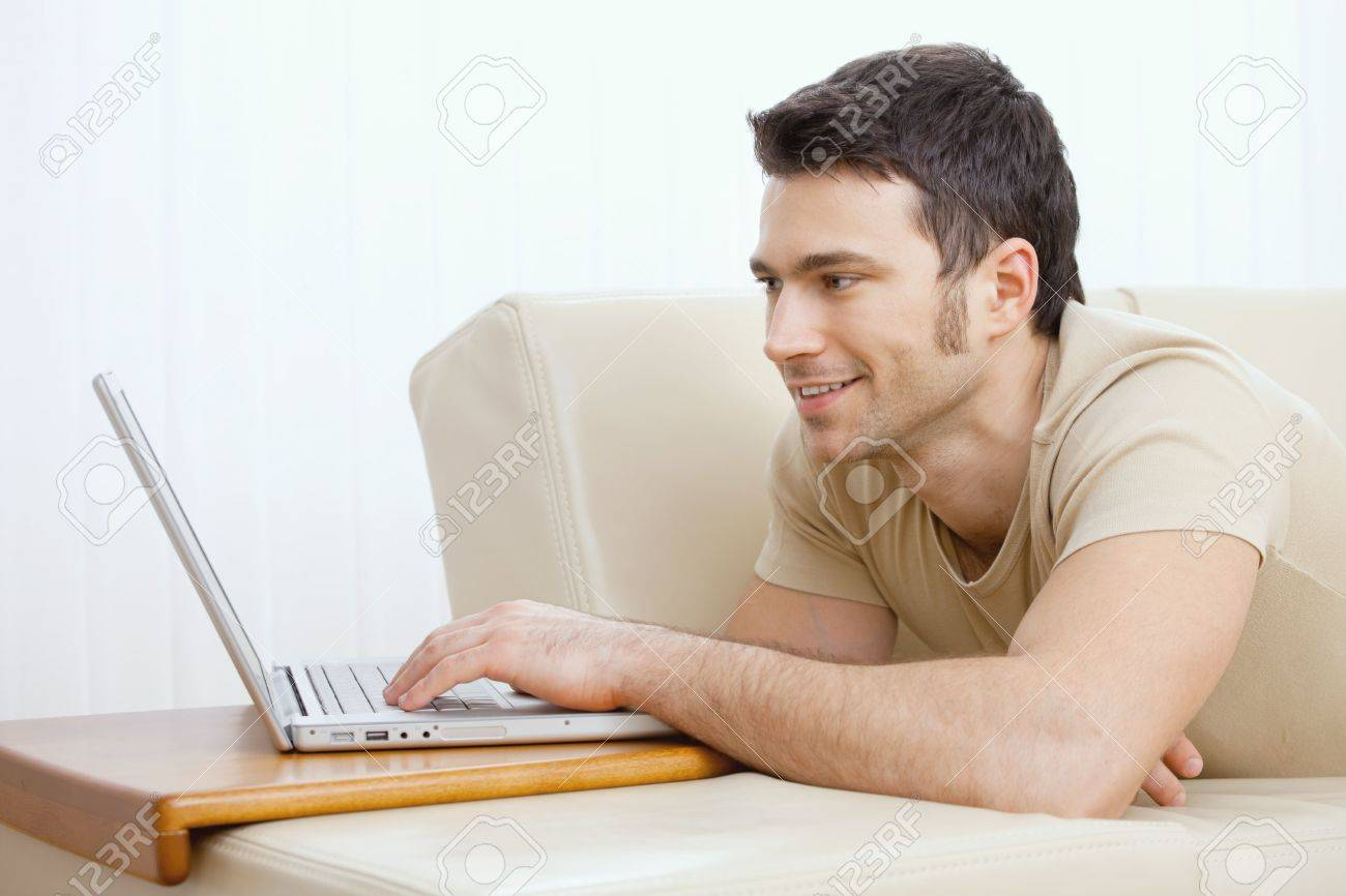 Happy young man laying on sofa at home using laptop computer, smiling. Stock Photo - 5851267