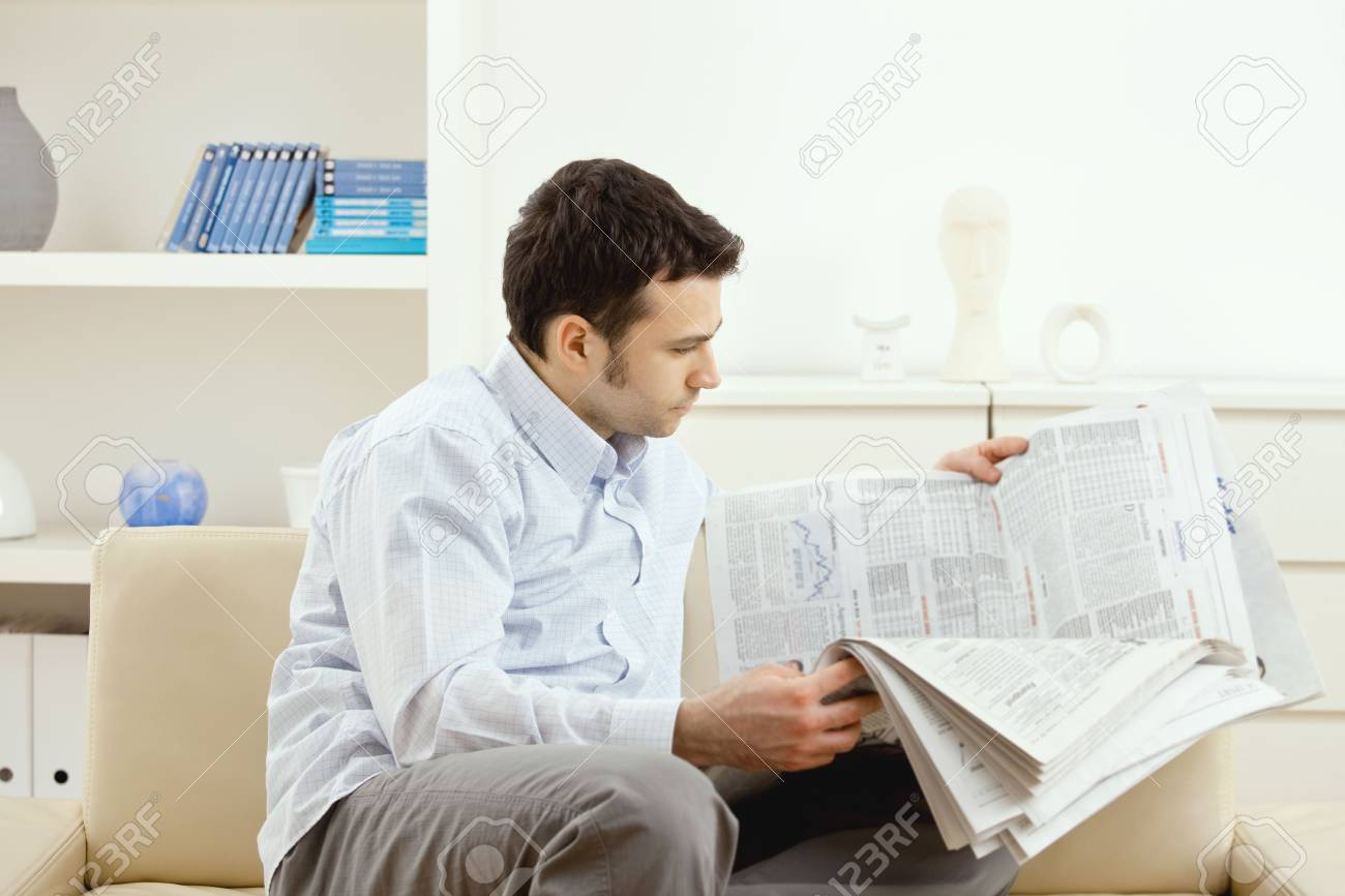 Handsome young man reading newspaper. Stock Photo - 5851276