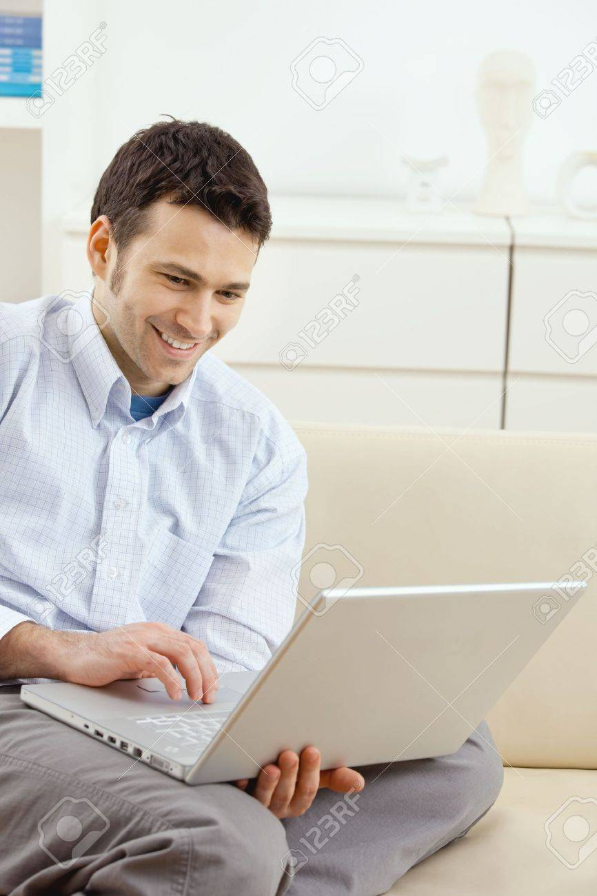 Happy young man sitting on couch and working on laptop computer at home, smiling. Stock Photo - 5851324