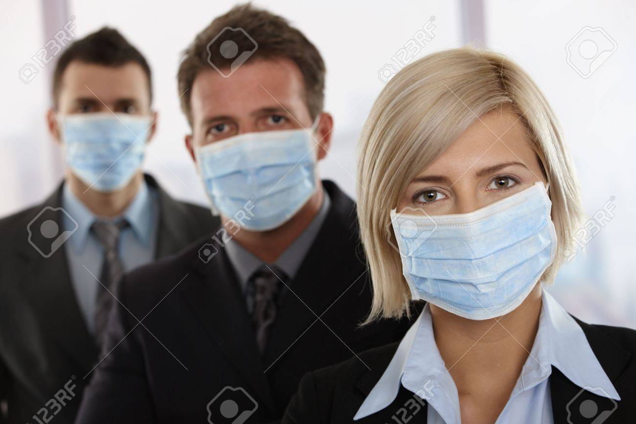 Business people fearing h1n1 swine flu virus wearing protective face mask and standing in a row. Stock Photo - 5899112