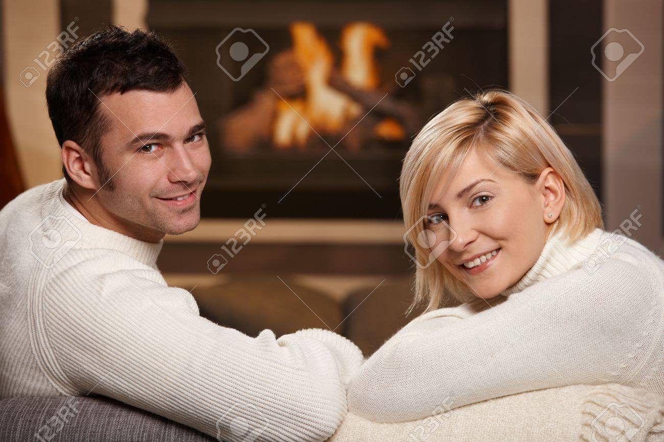 Young romantic couple sitting on sofa in front of fireplace at home, looking back, smiling. Stock Photo - 5899212