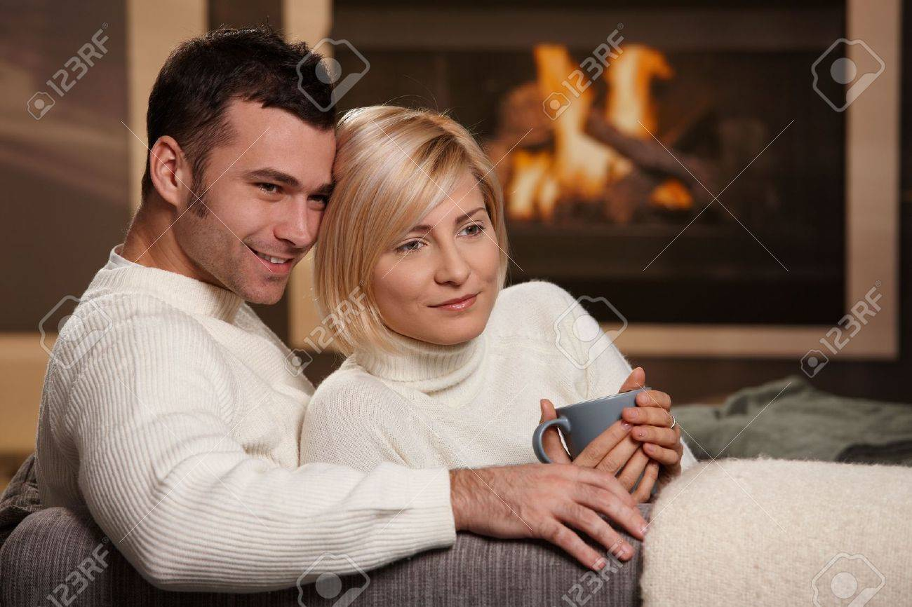 Young love couple hugging on sofa in front of fireplace at home, looking away, smiling. Stock Photo - 5899205