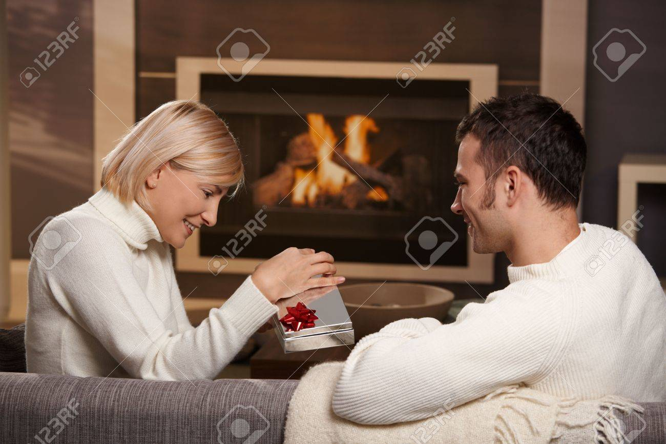 Young romantic couple sitting on couch in front of fireplace at home, man giving gift, side view. - 5899221