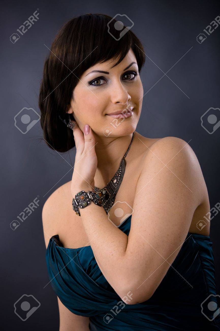 Closeup portrait of beautiful young woman wearing dark blue evening dress with necklace and bracelete, smiling and looking at camera. Stock Photo - 5908733