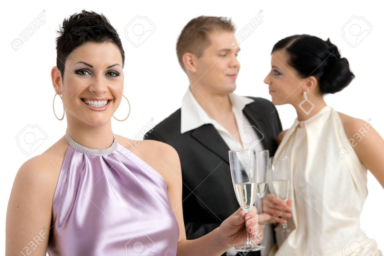 Happy young woman dressed for party holding a glass of champagne, smiling. Couple flirting on the background. Isolated on white background, selective focus. Stock Photo - 5908736