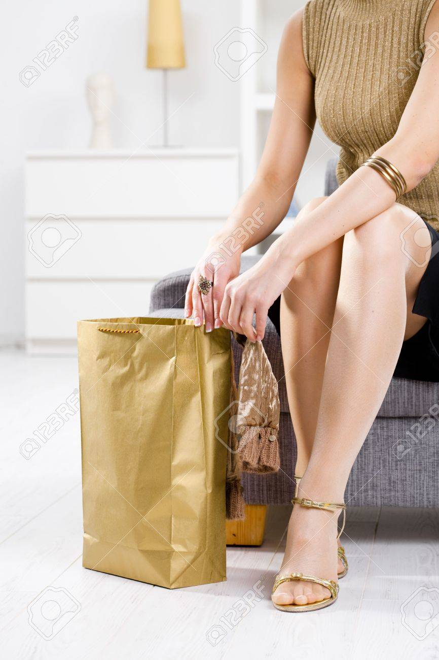 Closeup photo of female hands packing out from shopping bag. Legs in stockings and gold color shoes. Stock Photo - 5932509