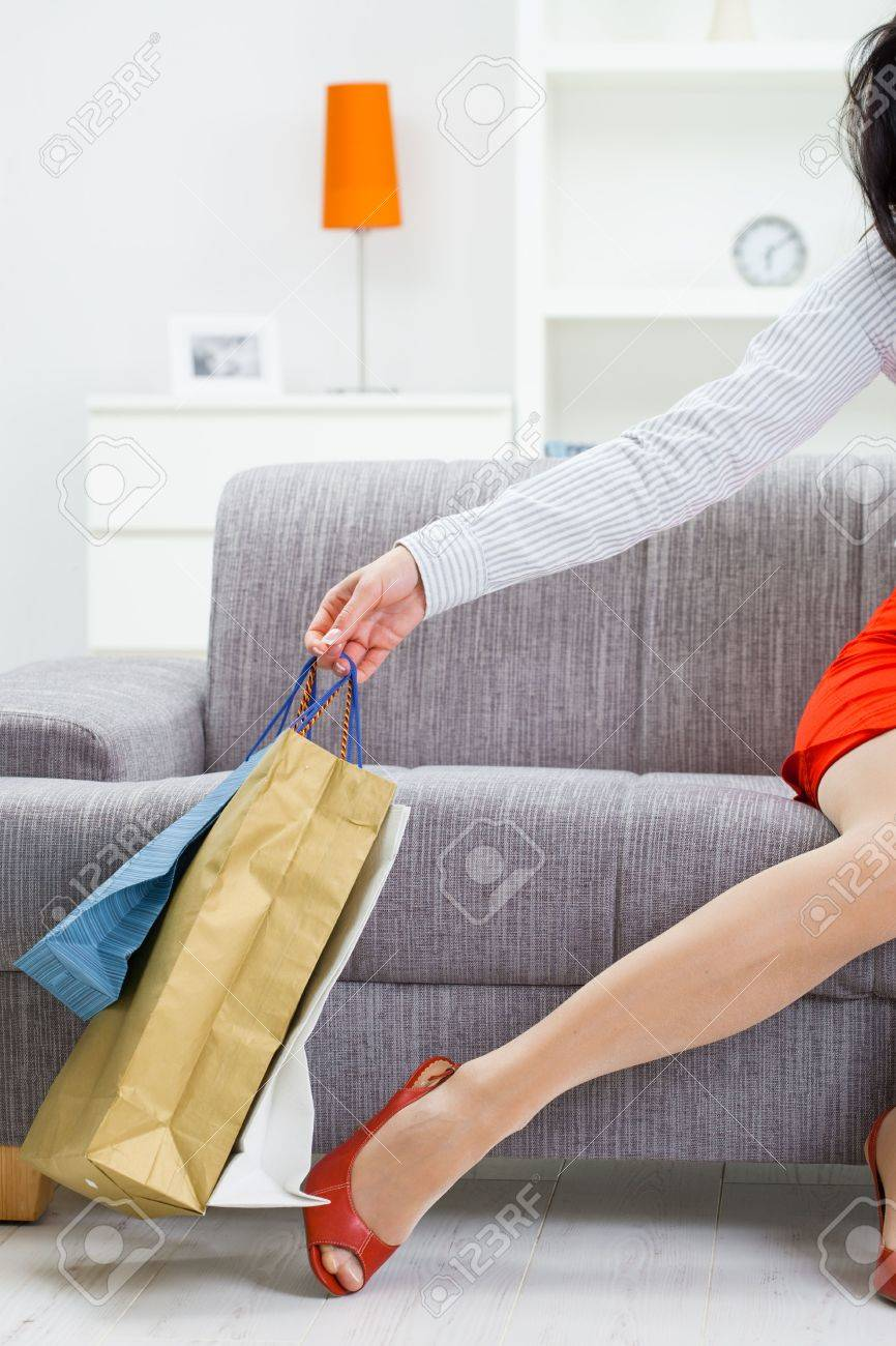 Female hand holding shopping bags, leg in stocking and red shoes. Stock Photo - 5932555