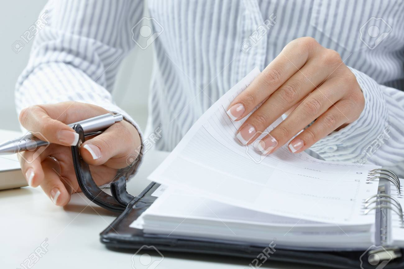Woman turning a page of personal organizer, focus on hands. Stock Photo - 5932505