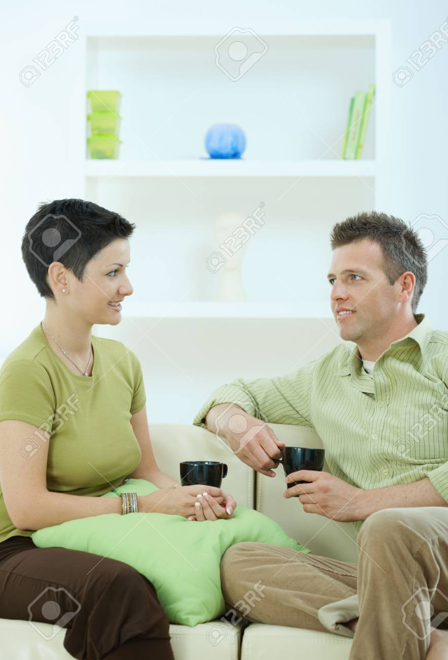 Young couple drinking coffee at home, sitting on couch, looking at each other, smiling. Stock Photo - 5934790