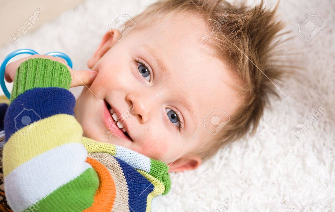 Happy baby boy ( 2 years old ) lying on back looking up to camera, smiling. Stock Photo - 5943335