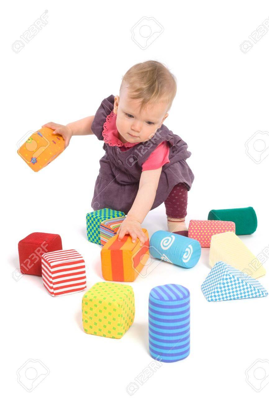 ddad229a99fc8 Banque d images - LES JOUETS SONT LIBÉRÉE DE PROPRIÉTÉ. Petite fille de bébé  (9 mois) joue avec les blocs de jouet. Isolées sur blanc.