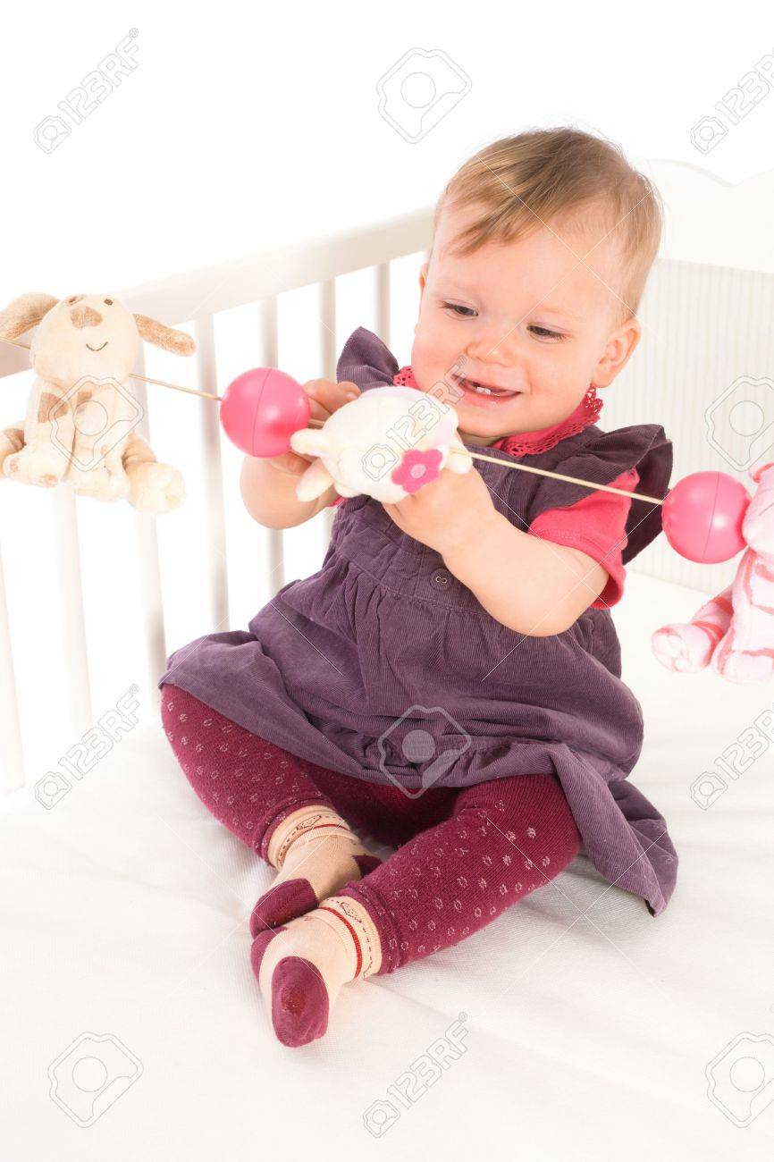 Cute baby girl (1 year old) sitting on crib, holding soft toys. Isolated on white, smiling. Toys are offically property released. Stock Photo - 5943601