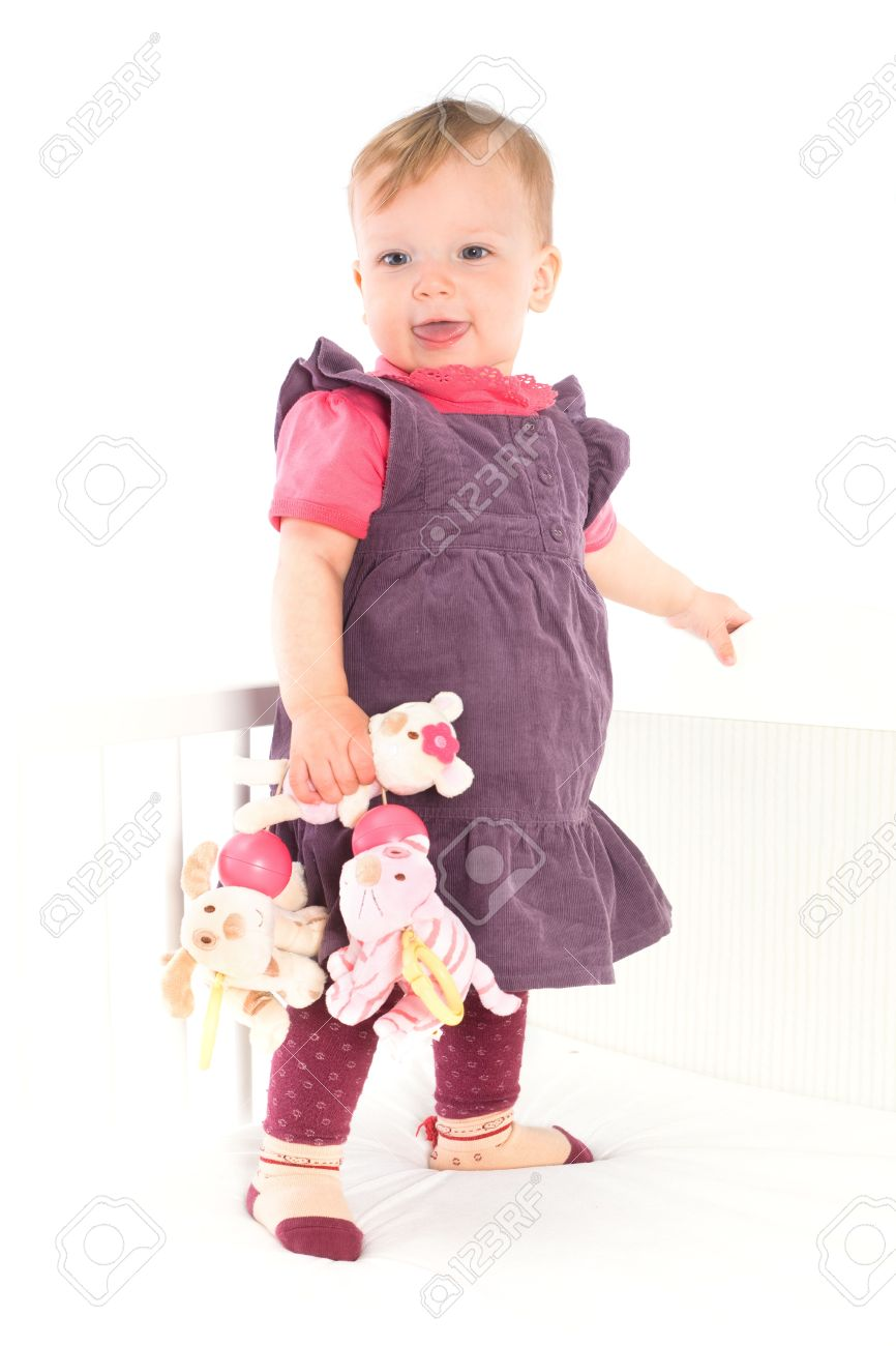 Cute Baby Girl 1 Year Old Standing On Crib Holding Soft Toys