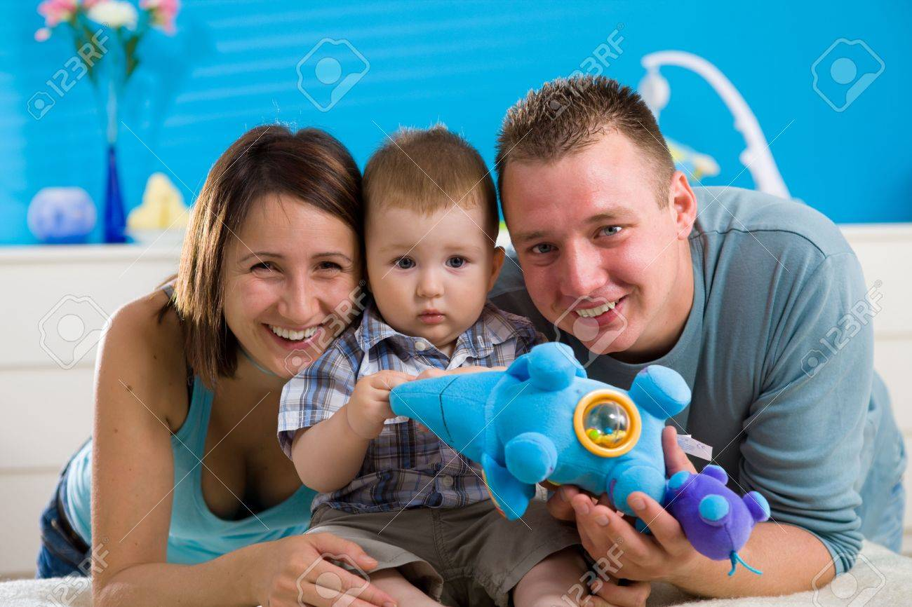 Portrait of happy family at home. Baby boy ( 1 year old ) and young parents father and mother sitting on floor and playing together at children's room, smiling. Stock Photo - 5943598