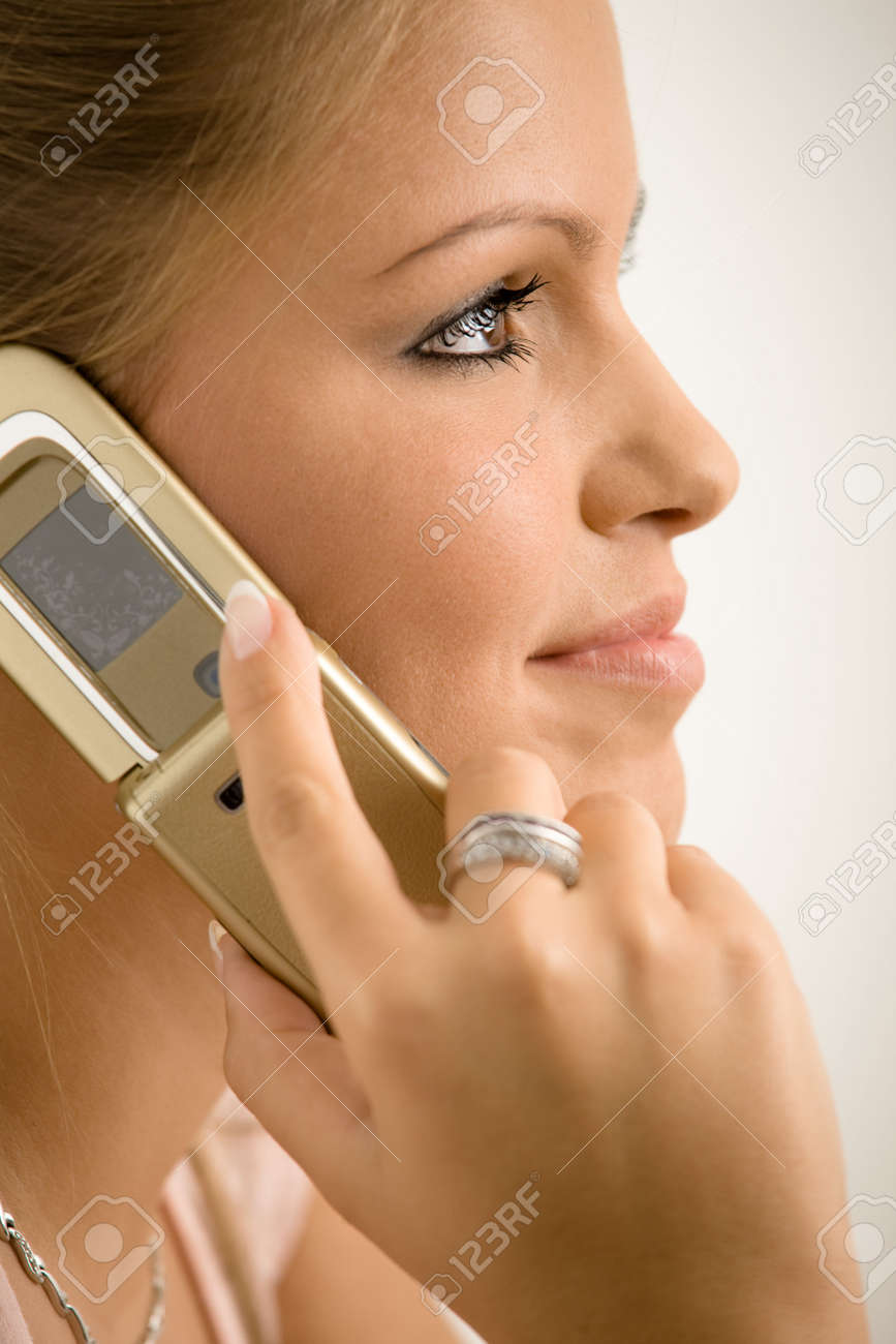 Closeup portrait of beautiful smiling college girl talking on mobile phone, isolated on white background. Stock Photo - 5982558