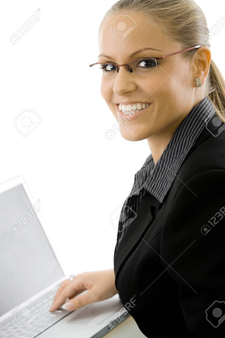 Happy young businesswoman sitting at desk working on laptop computer, smiling, isolated on white background. Stock Photo - 5982616
