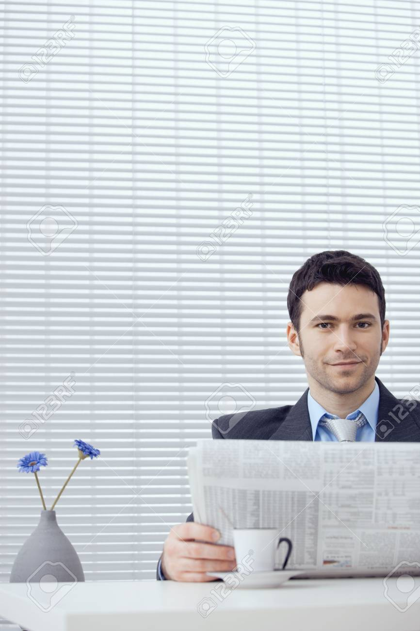 Young businessman having coffee break, sitting at office desk and reading newspaper. Copy space. Stock Photo - 5982770