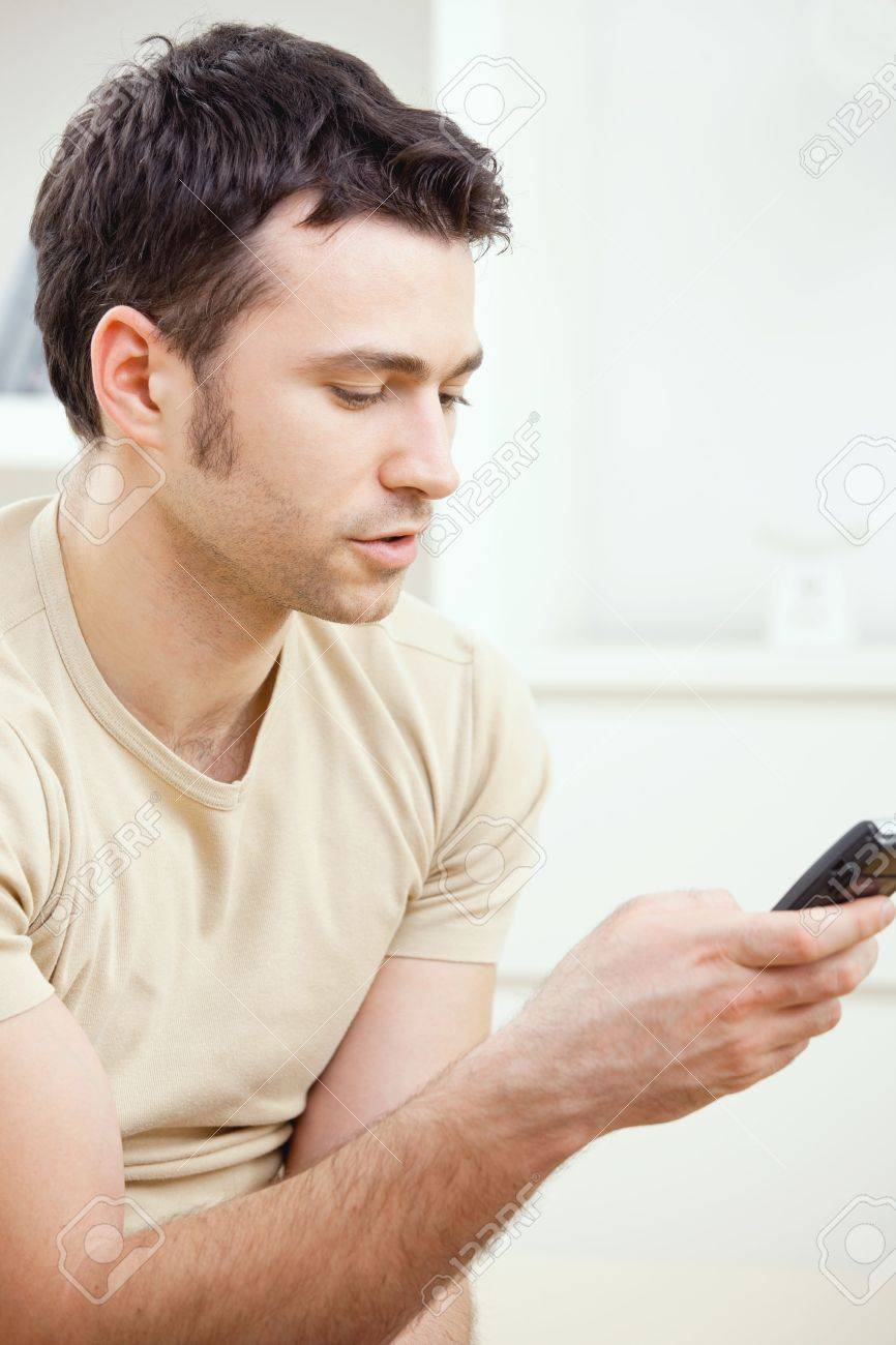 Young handsome man writting SMS on mobile phone. Stock Photo - 5982764