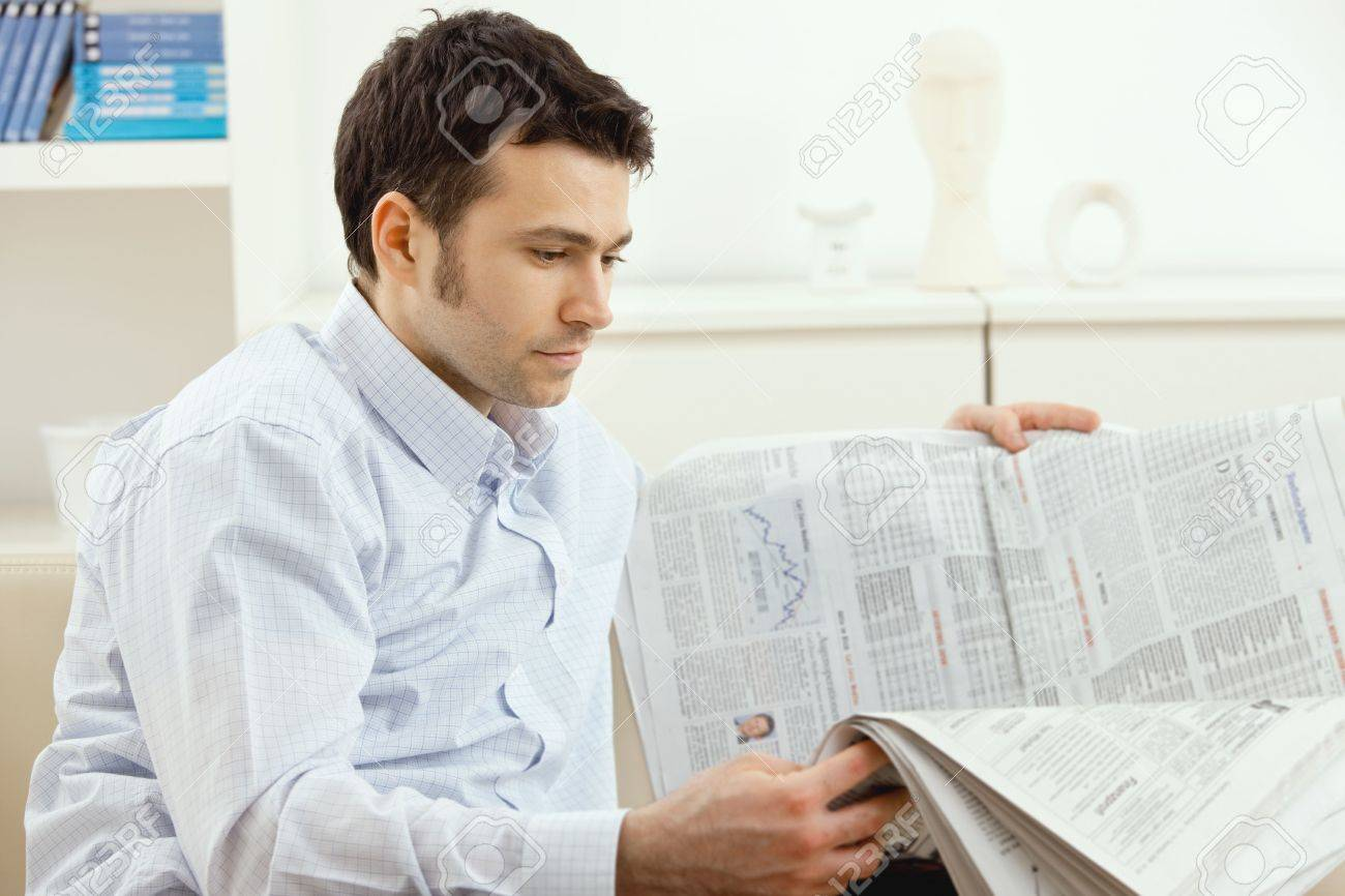 Handsome young man reading newspaper. Stock Photo - 5982760