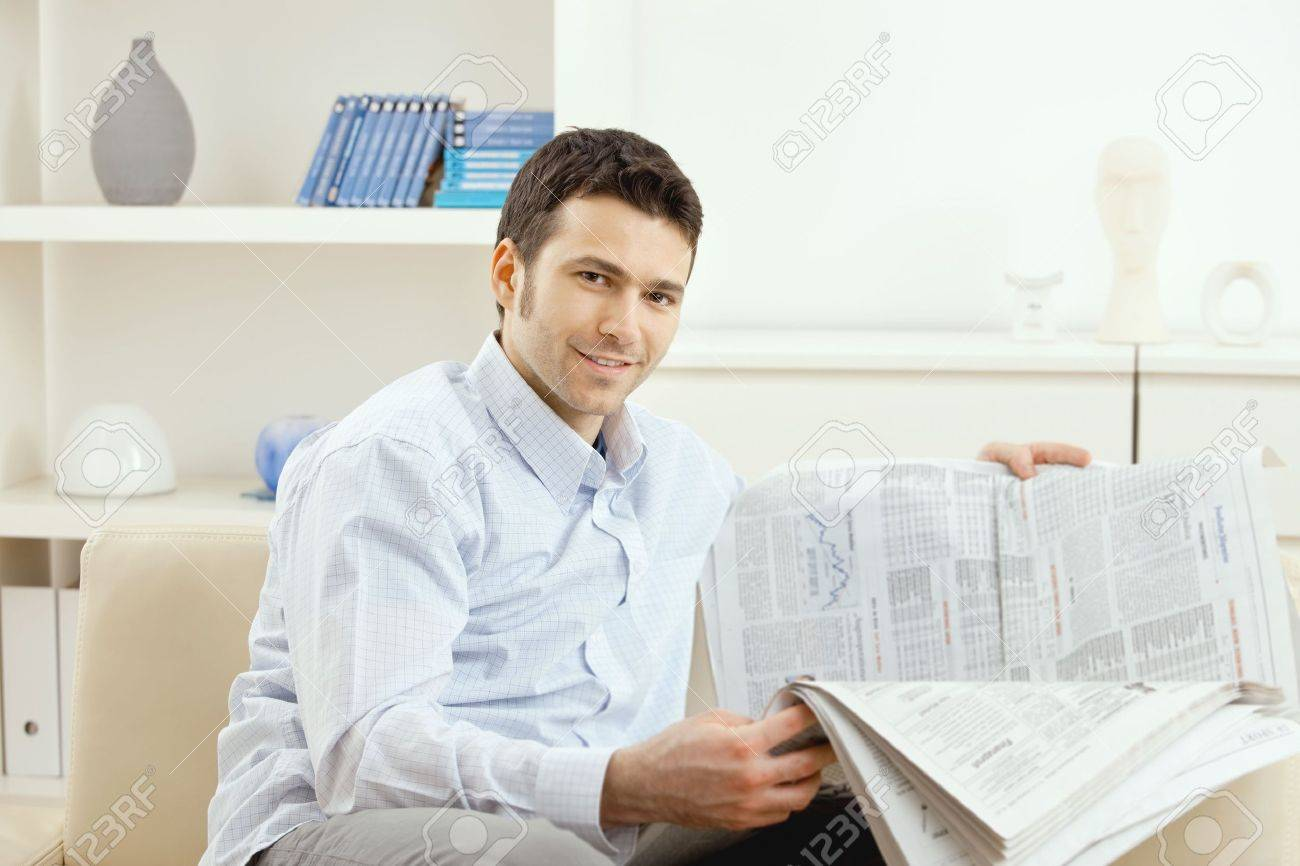 Casual young businessman reading business news, sitting on couch at home, looking at camera, smiling. Stock Photo - 5982837