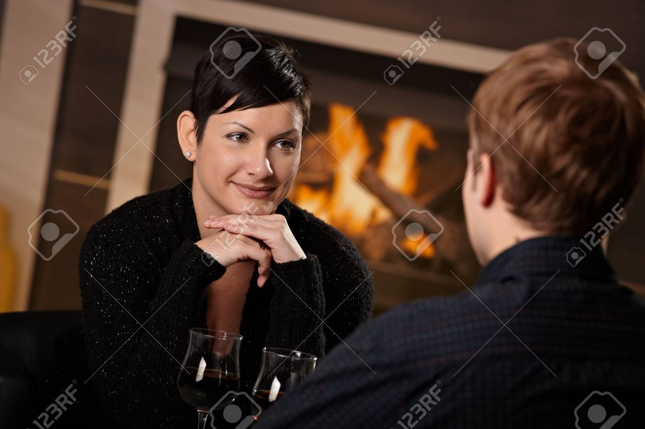 Young romantic couple dating, sitting in front of fireplace at home, drinking red wine. Stock Photo - 5983188