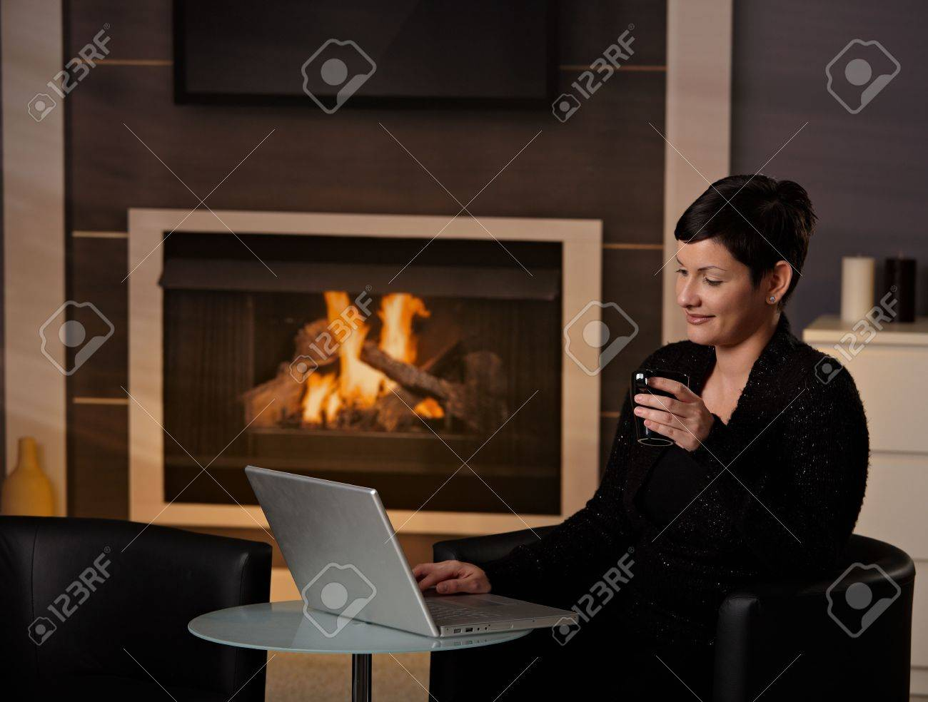 Young Woman Sitting In Front Of Fireplace At Home On A Cold Winter ...