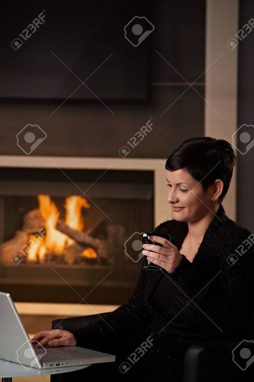 young woman sitting in front of fireplace at home on a cold winter