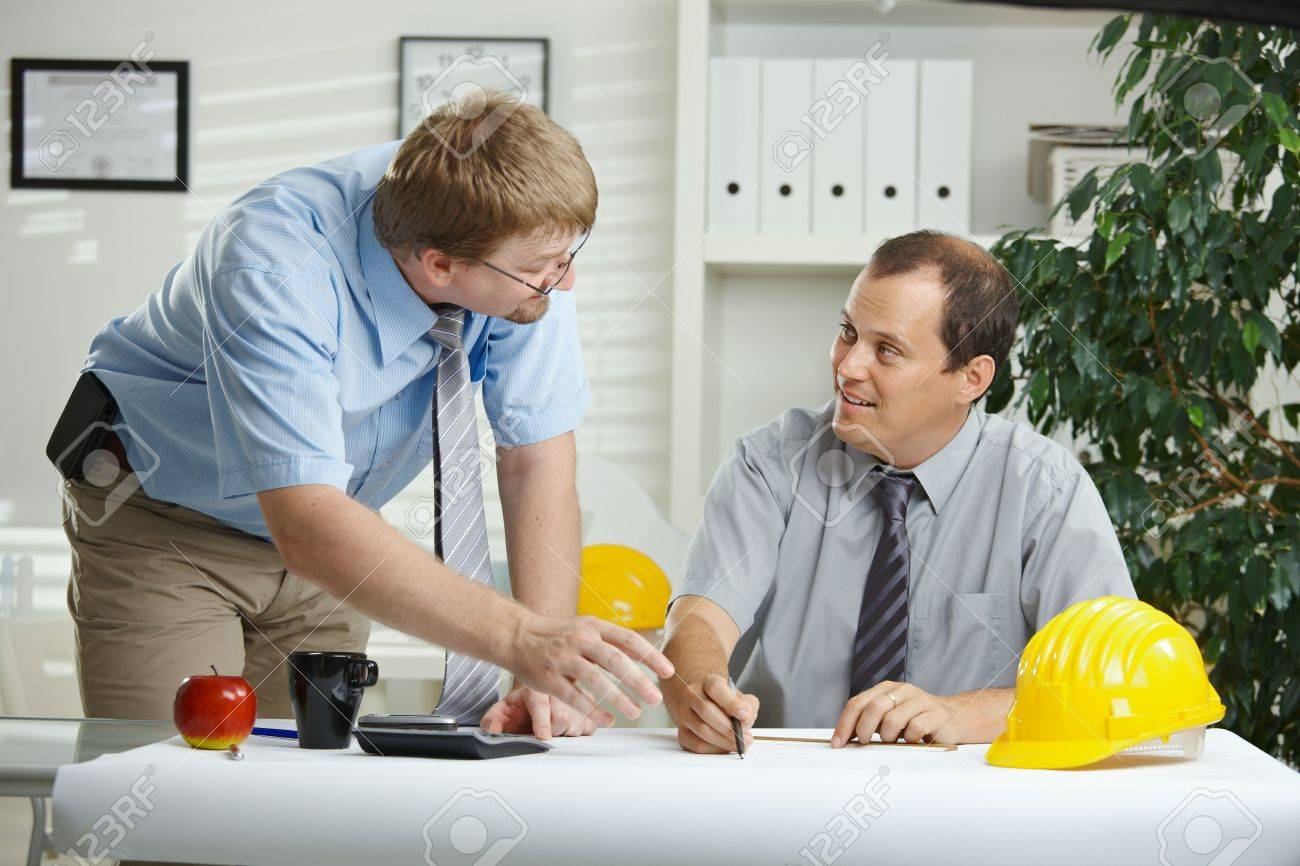 Architects working at office - planning and talking over blueprint on desk. Stock Photo - 5983155