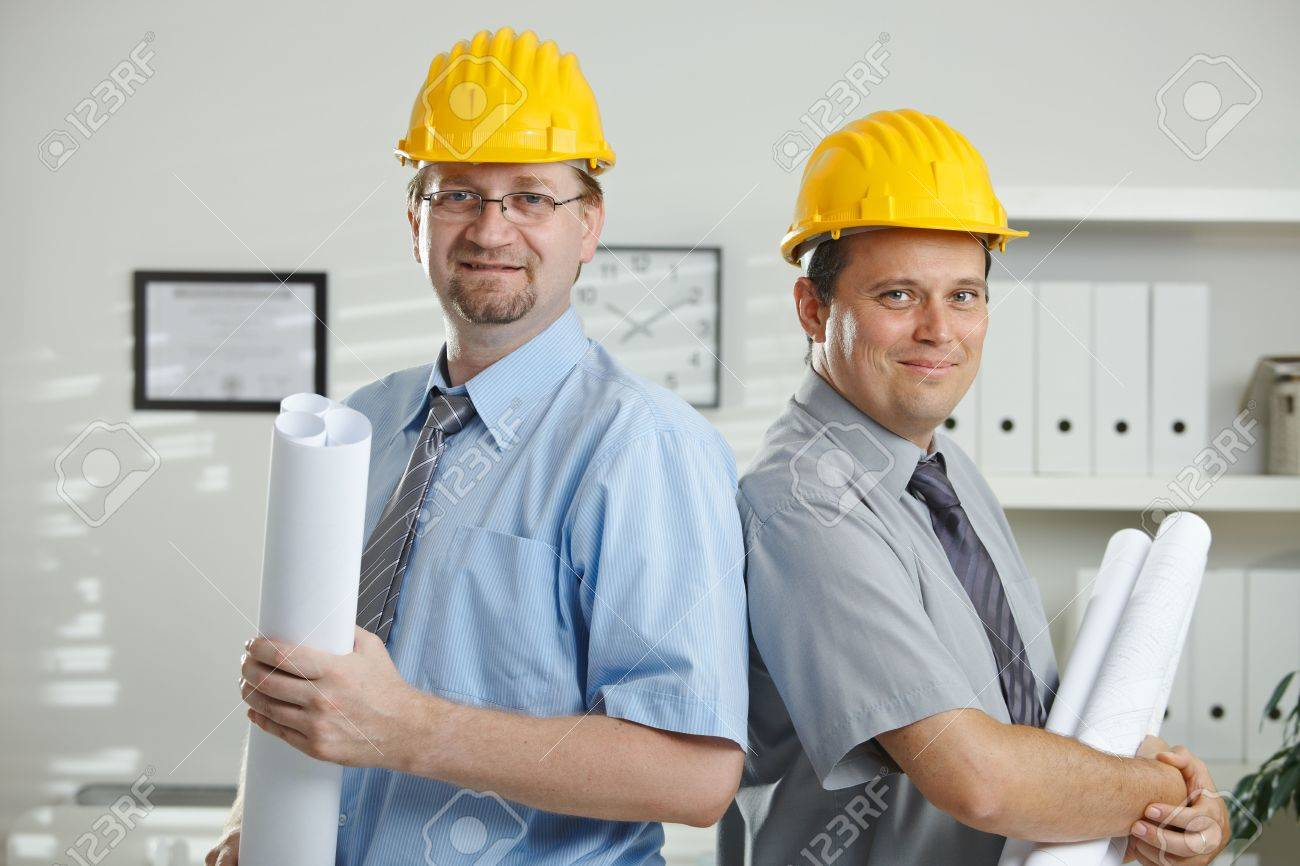 Architects in hardhats posing for teamphoto at office. Stock Photo - 5983179
