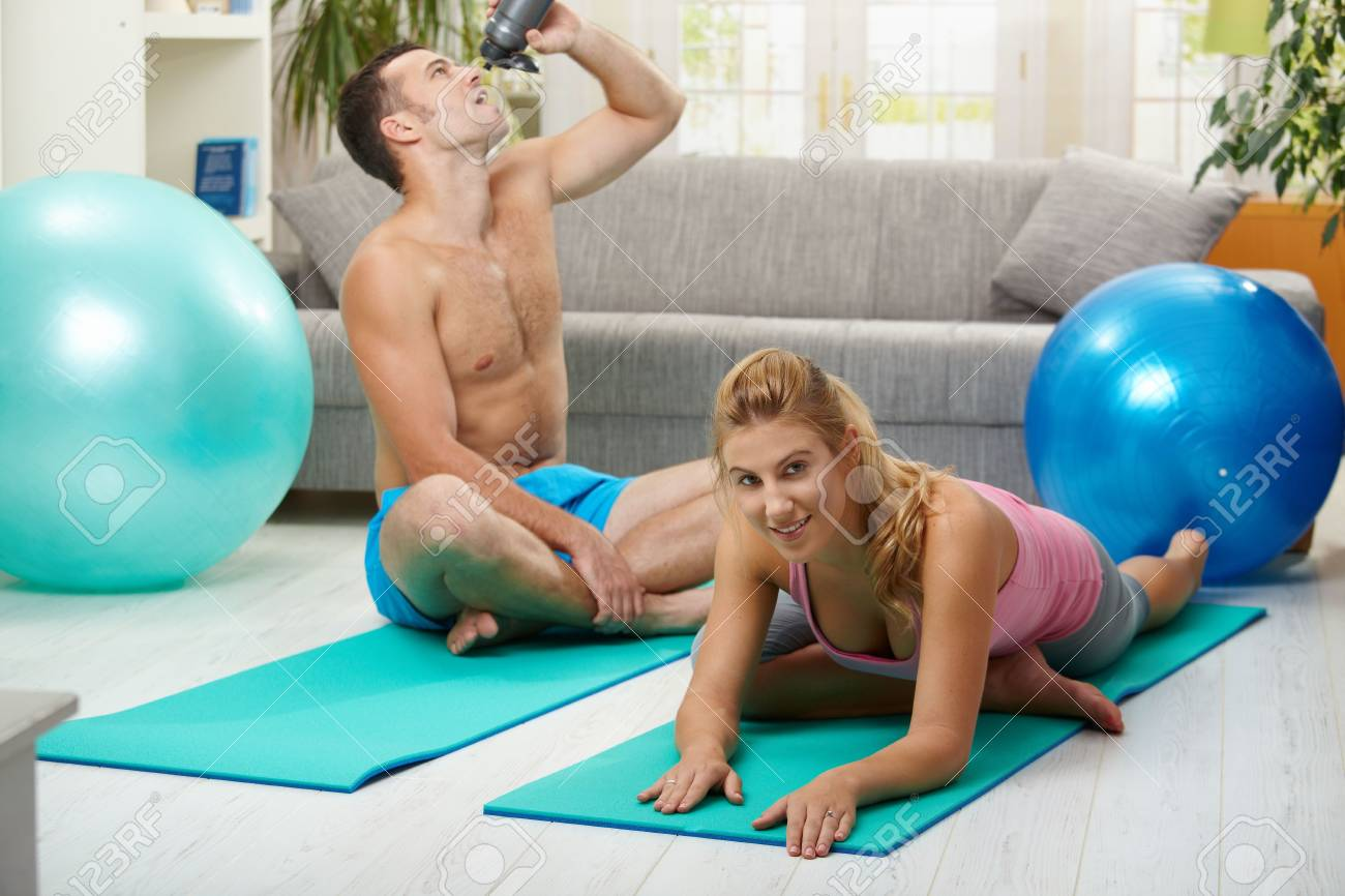 Young women doing streching exercise on fitness mat, muscular man drining water in the background. Selective focus on woman. Stock Photo - 6026628