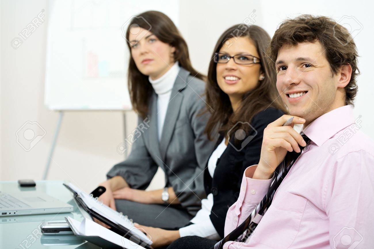 Group of smiling businesspeople sitting in row on training and looking at trainer positively. Stock Photo - 6041114