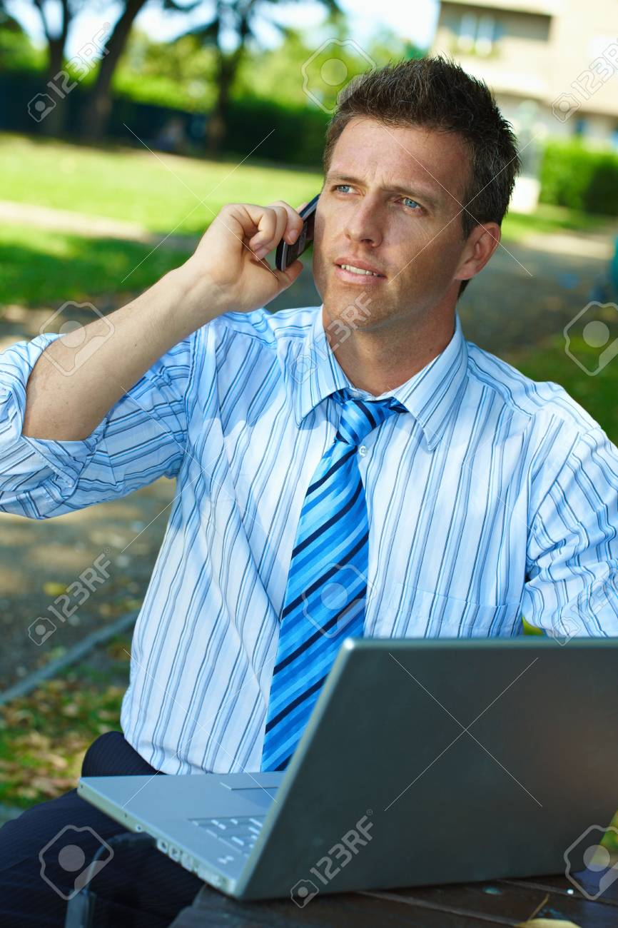 Businessman working outdoor in park, using laptop and talking on mobile. Stock Photo - 6220062