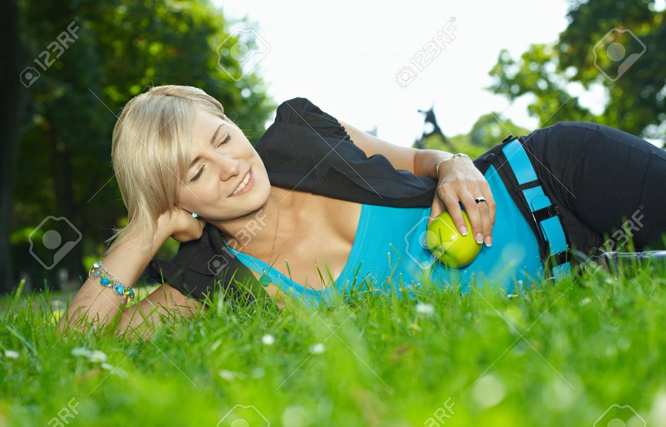Portrait of young woman lying in grass with eyes closed, smiling. Stock Photo - 6220693