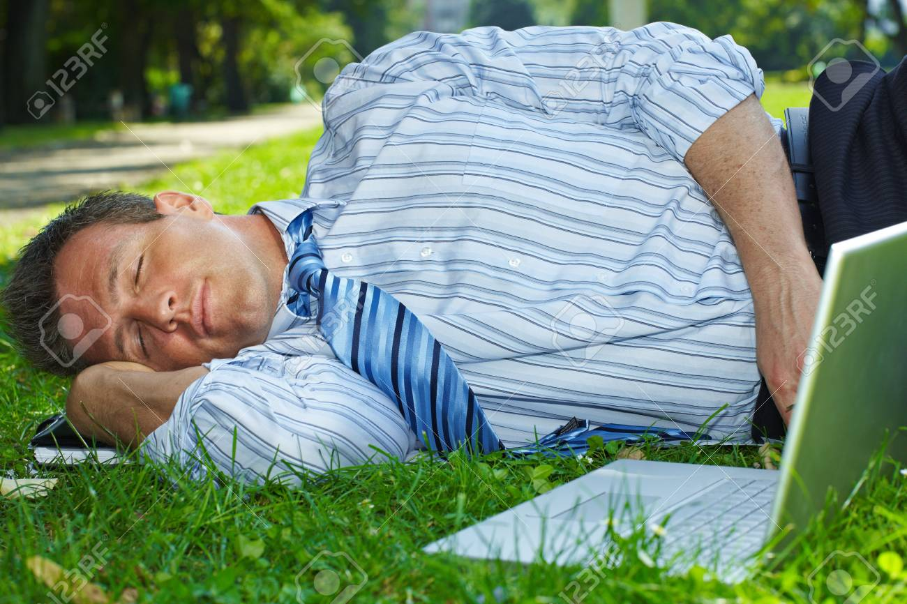 Closeup portrait of relaxed businessman lying in grass beside laptop computer. Stock Photo - 6220692