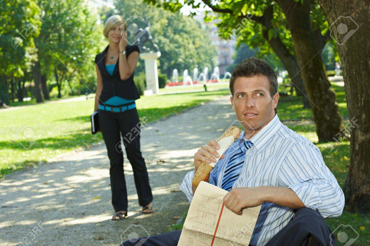 Casual businessman sitting on bench in park eating sandwich, holding newspaper. Stock Photo - 6220026