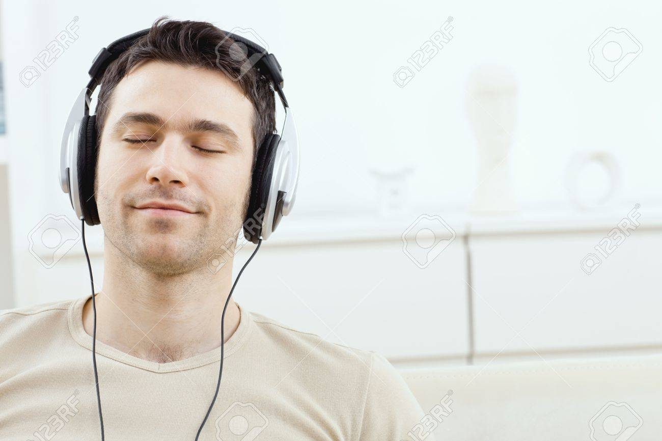 casual man listening music with headphones at home relaxing stock