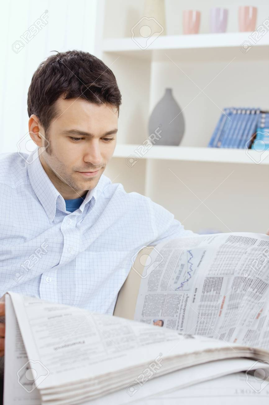 Handsome young man reading newspaper. Stock Photo - 6224422