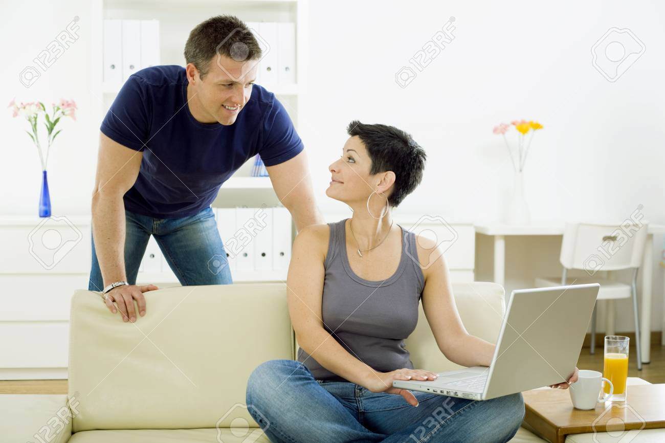 Happy young couple browsing internet on laptop computer at home, smiling. Stock Photo - 6235783