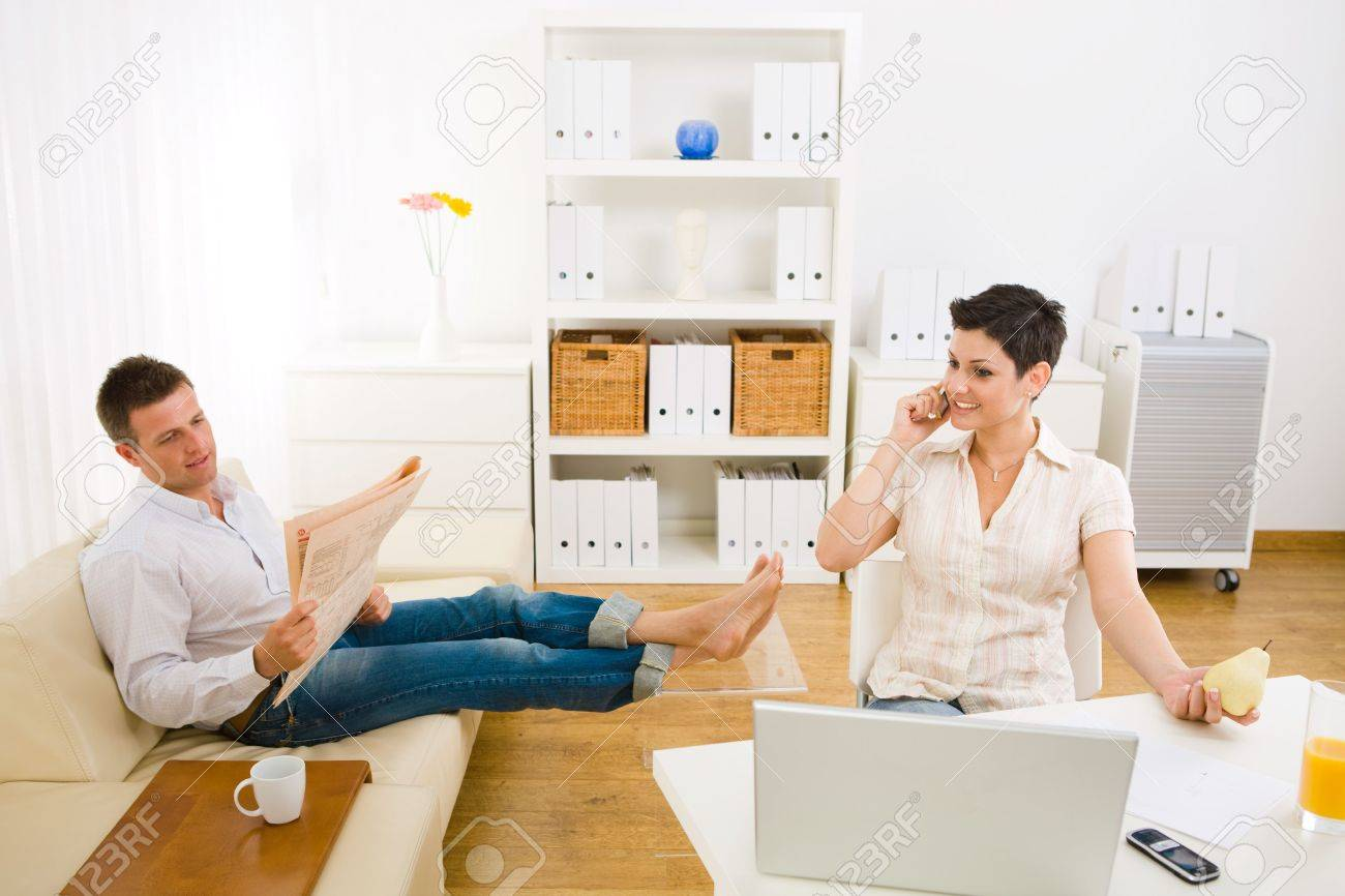 Young woman talking on mobile phone at home, smiling. Man reading newspaper in the background. Selective focus on the woman. Stock Photo - 6235801