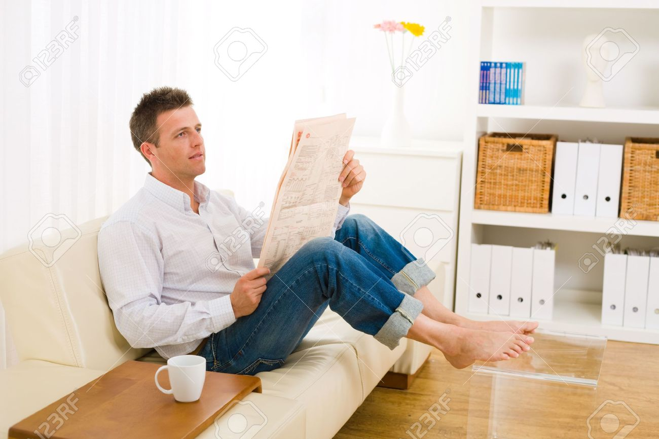 Casual man wearing white shirt and jeans, sitting on couch barefooted and reading newspaper. Stock Photo - 6235823