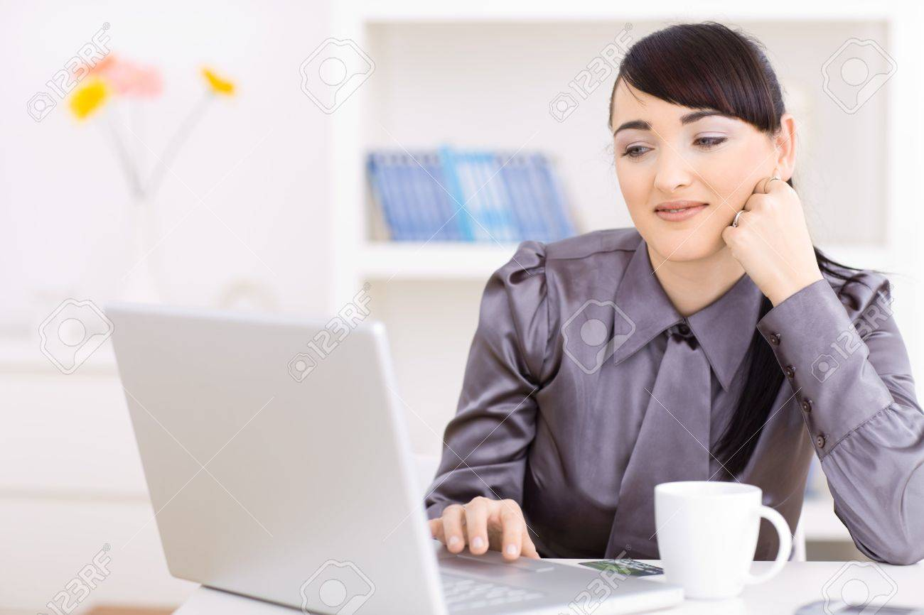 Portrait of attractive young businesswoman thinking over her laptop computer, leaning on her hand. Stock Photo - 6235748