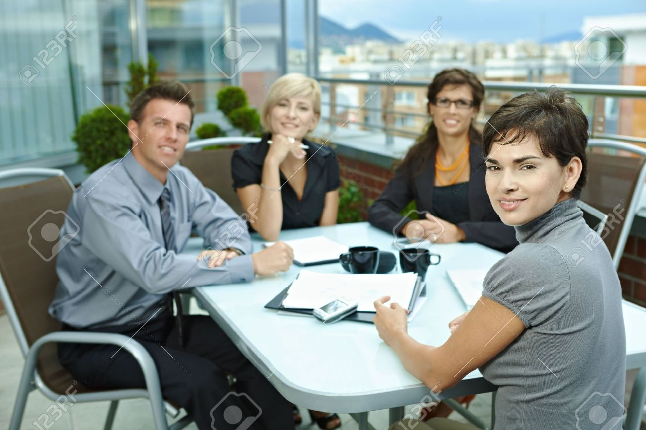group of young business people sitting around table on office