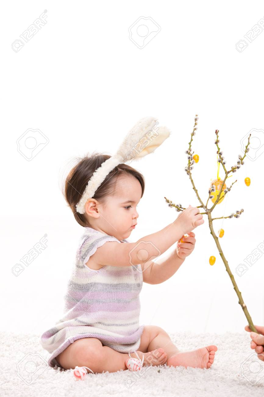 Baby girl in easter bunny costume, playing with easter eggs hanging from willow branch. Isolated on white background. Stock Photo - 6254473