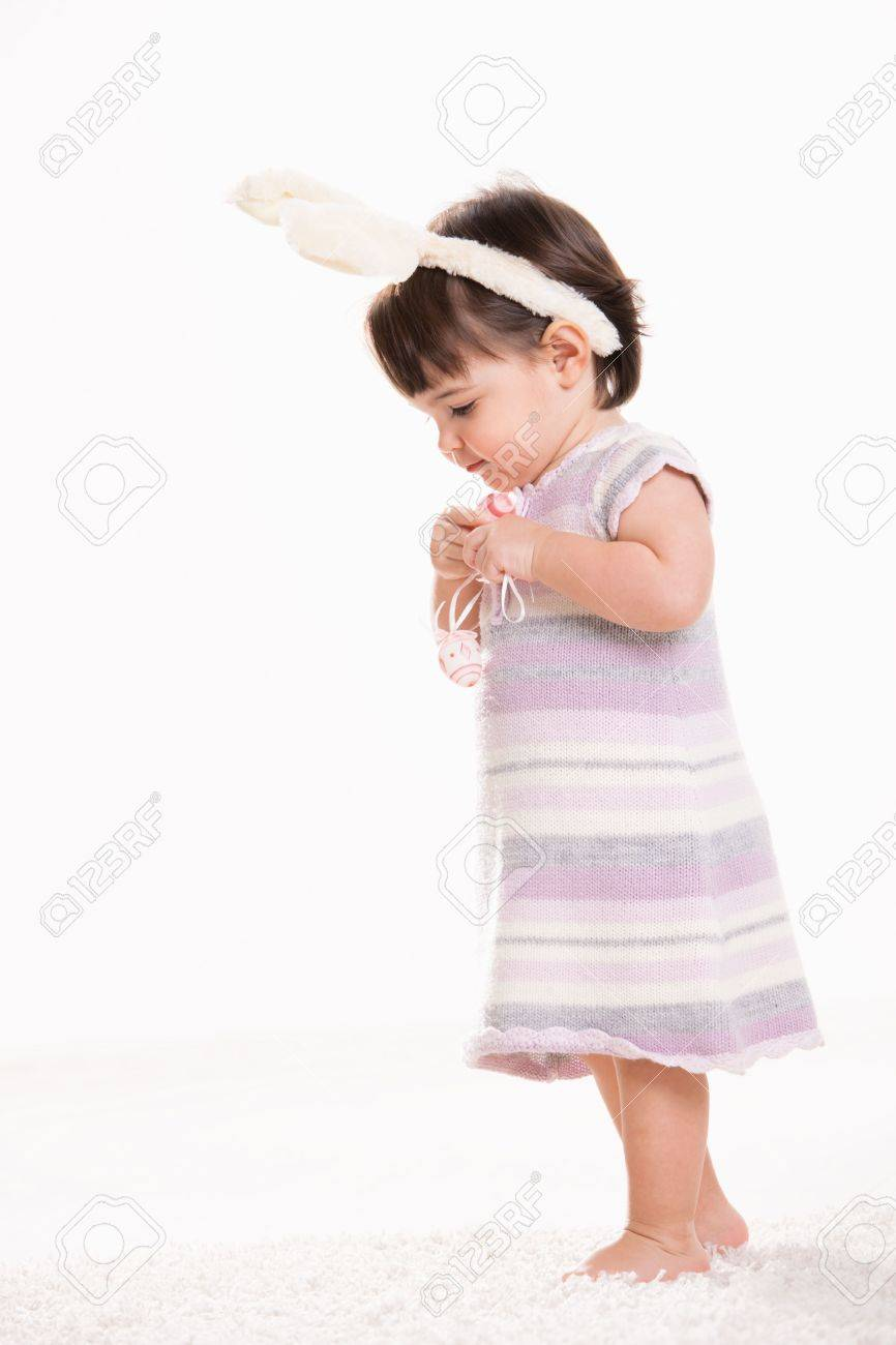 Profile portrait of baby girl in easter costume standing on carpet, holding easter eggs, looking down. Isolated on white background. Stock Photo - 6254449