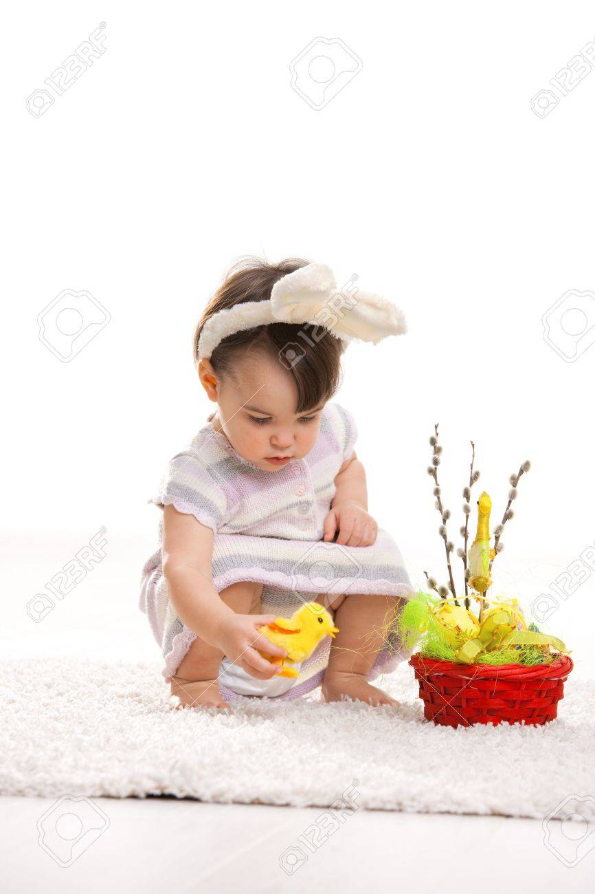 Baby girl in easter bunny costume, playing with toy chicken beside easter basket. Isolated on white background. Stock Photo - 6254447